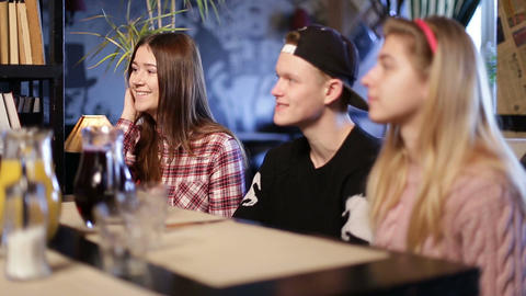 Happy teenage friends sitting and chatting in cafe Footage