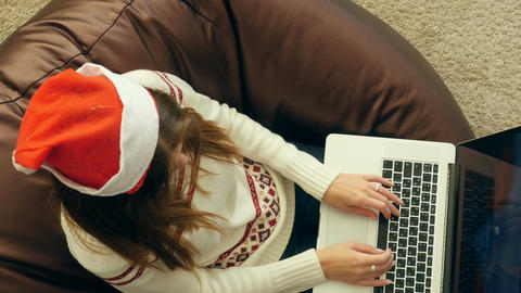 Girl in christmas cap using laptop on soft chair Footage