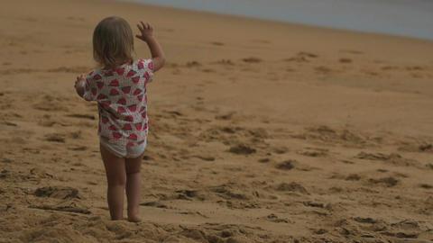 Little girl steps on sandy beach Footage