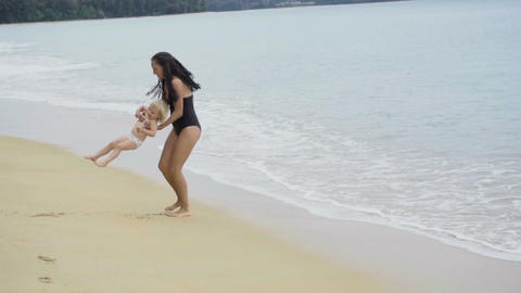 Mother turns her little girl on arms and sandy beach Footage