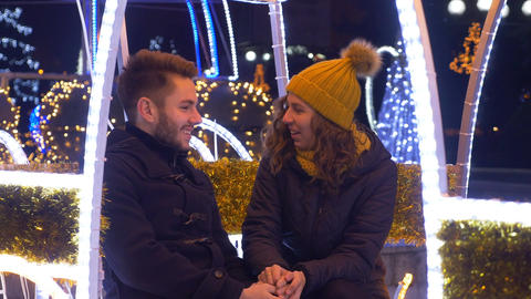 Lovers holding hands and laughing at each other in Christmas fair Footage