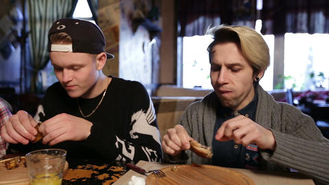 Hipsters eating delicious roasted chicken wings Live Action