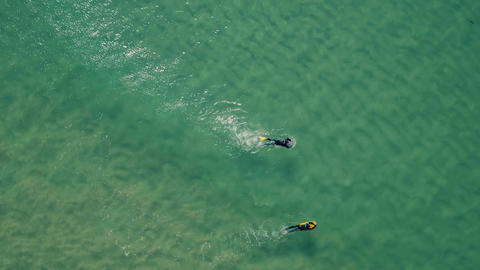 Aerial View of Surfers Riding Green Ocean Waves Footage