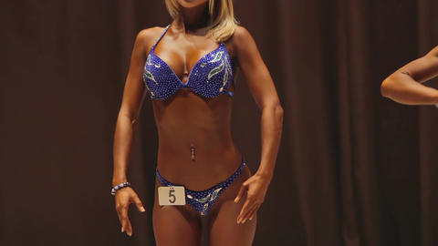 Beautiful fitness show participant demonstrating gorgeous feminine strong body Live Action