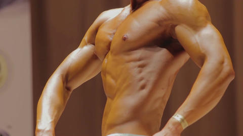 Male bodybuilder showing physique in relaxed side and rear lat spread poses Footage