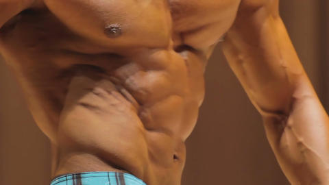 Bodybuilder taking relaxed contest poses to demonstrate ripped muscular torso Footage