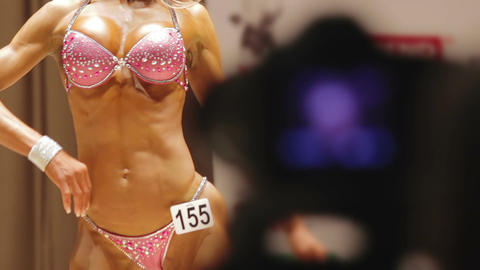 Female bodybuilder demonstrating ideal muscular body in relaxed front poses Footage