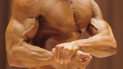 Bodybuilder demonstrating strong body in side chest and rear double bicep poses Footage