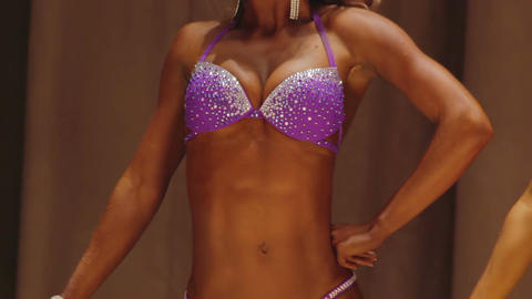 Female bodybuilder taking relaxed poses to show perfect body at competition Footage