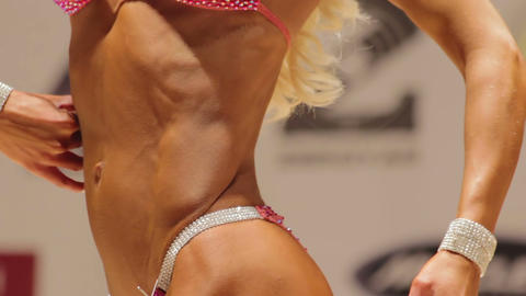 Beautiful female bodybuilder taking side and rear poses to demonstrate fit body Footage