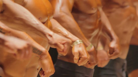 Lineup of strong male bodybuilders demonstrating massive muscles at competition Live Action