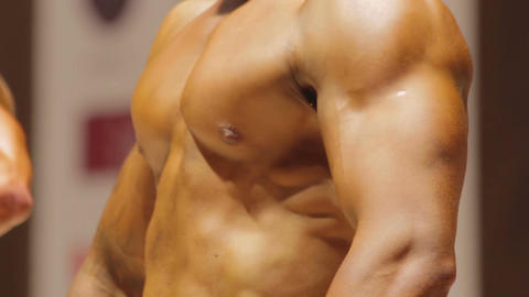 Strained chest and abs muscles of strong bodybuilder competing for leadership Live Action