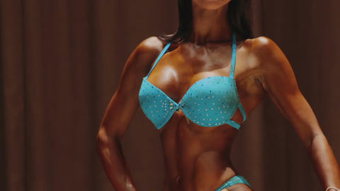 Sexy muscular body of feminine fitness model performing at bodybuilding contest Live Action