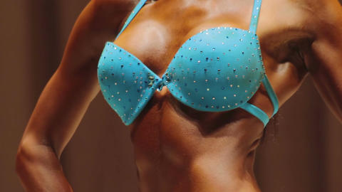 Beautiful feminine body, sexy breasts of fitness model at figure competition Live Action