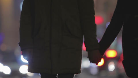 Two people in love holding hands, walking slowly along busy city street at night Live Action