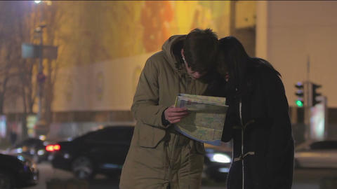 Young people travel abroad, lost in megalopolis, searching right way on city map Live Action