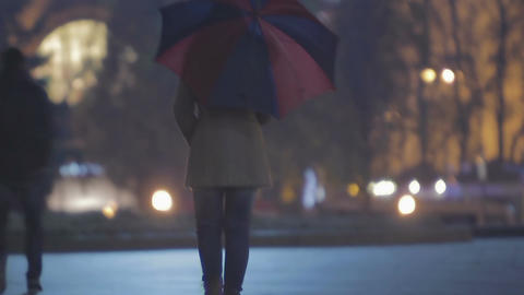 Sad woman with umbrella walking and waiting on someone in city, melancholy Footage