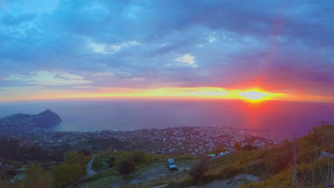 Wonderful ocean sunset, view on city from mountain peak, heavy clouds timelapse Footage
