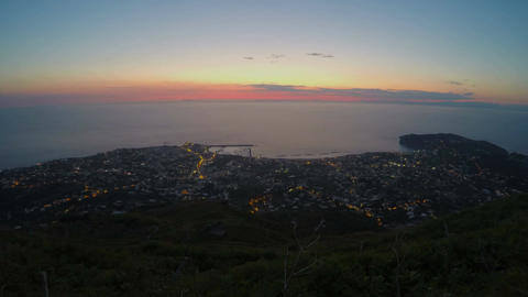 Pink sky above ocean, night city lights, electricity consumption in megalopolis Live Action