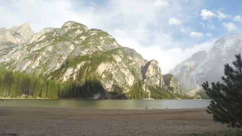 Timelapse of clouds above mountains and lake Pragser Wildsee in Italy, tourism Footage