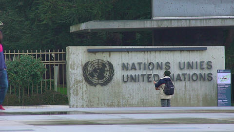 Male tourist taking selfie by United Nations Office at Geneva, viewing landmarks Live Action