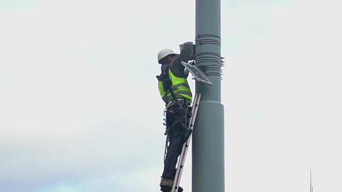 Municipal engineer standing on ladder at height, hazardous maintenance work Footage