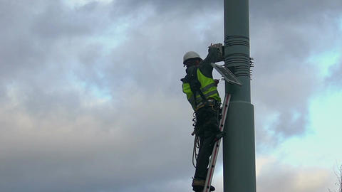 Electrical engineer checking wires, fixing street light system, dangerous job Footage
