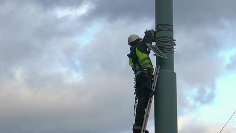 Maintenance worker servicing street video surveillance system, work at height Footage