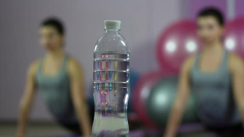 Defocused flexible woman exercising in gym, fresh water for healthy fit body Live Action