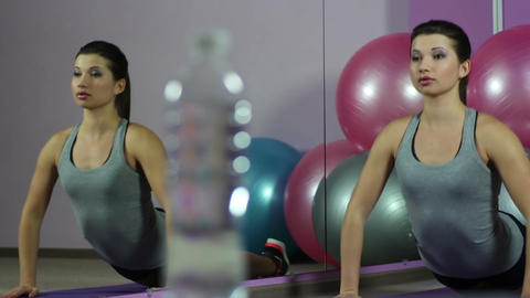 Focus changing from flexible woman stretching in gym to bottle of fresh water Live Action