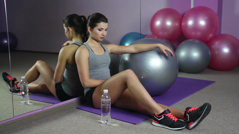 Tired woman having rest after intensive workout in gym, drinking fresh water Footage