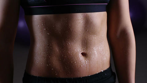 Wet belly of sportive woman covered with water drops, active training in gym Live Action