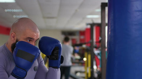 Professional male boxer practicing punches on boxing bag, working hard in gym Footage