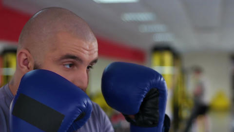 Face closeup of man in boxing gloves punching sparring partner during workout Footage