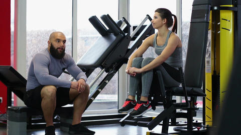 Couple sitting in gym, bored while waiting for coach, not talking after fight Footage