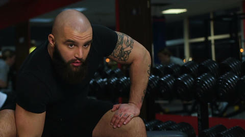 Tattooed muscular male athlete doing dumbbell exercises, working out in gym Footage