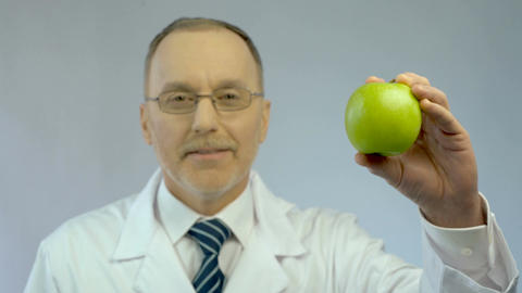 Male nutritionist showing fresh apple at camera, offering patient healthy diet Footage