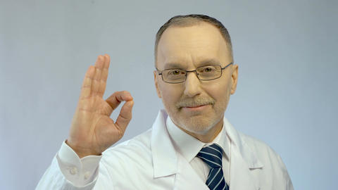 Male physician smiling, showing OK gesture, sure of successful treatment results Live Action