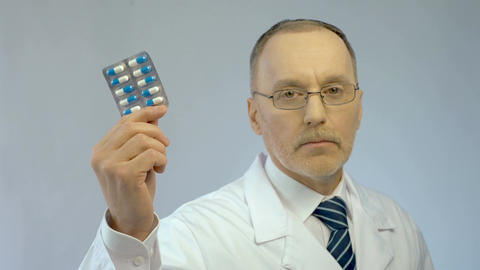 Serious physician holding pills in hand, recommending effective medication Live Action