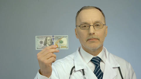 Male therapist showing one hundred dollars bill, paid health care services Footage