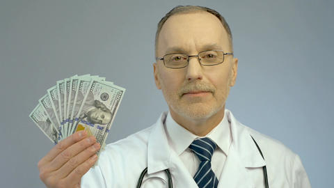 Doctor holding bundle of dollars, paid medicine, expensive health care services Footage