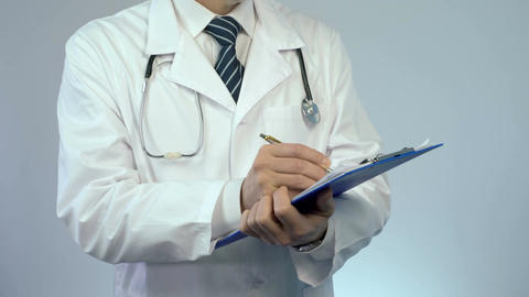 Professional physician writing in paper documents, keeping medical records Footage