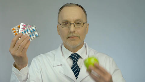 Nutritionist showing pills and fresh apple, offering to choose healthy lifestyle Footage