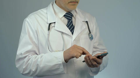 Hospital physician dialing number on smartphone, calling to consult patient Footage