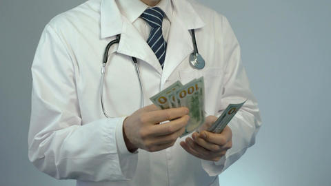 Male doctor counting money, paid health care services at private clinic, bribe Footage