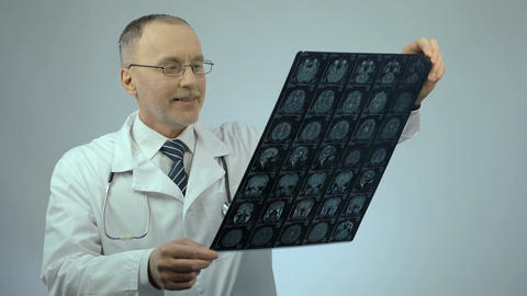 Happy smiling doctor checking MRI brain scan, satisfied… Stock Video Footage