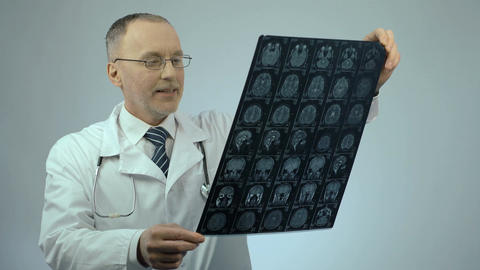 Happy smiling doctor checking MRI brain scan, satisfied with treatment results Live Action