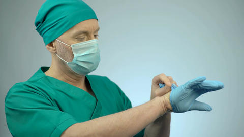 Nervous surgeon putting on medical gloves, preparing for serious operation Footage