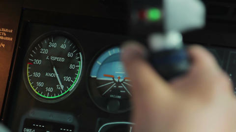 Rack focus of pilot hands steering plane and flight display with speedometer Live Action