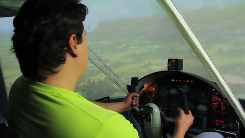 Young male sitting in cockpit, enjoying flight in plane simulator, hobby Footage